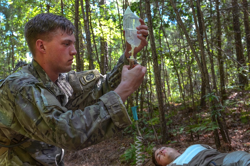 A soldier provides an IV to a role-playing casualty victim.