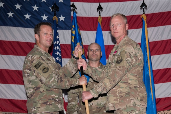 Brig. Gen. David Iverson, 332nd Air Expeditionary Wing commander and presiding officer, takes the 332nd Expeditionary Medical Group guidon from Col. Bradley Nielsen at a change of command ceremony, Aug. 3, 2018, at an undisclosed location in Southwest Asia.