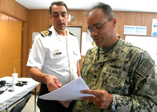 Military leaders converse while looking at a computer screen.