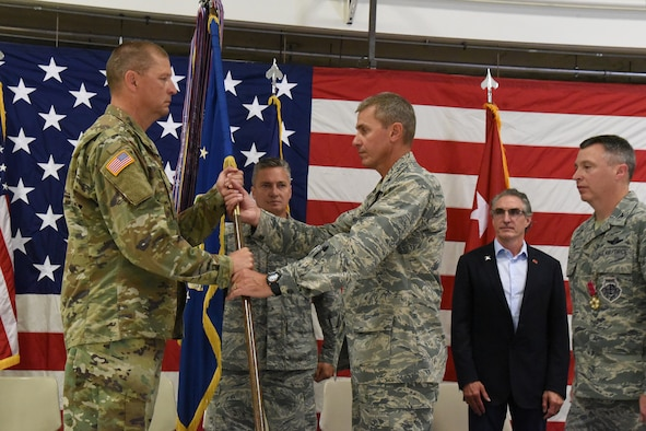 Maj. Gen. Al Dohrmann, the N.D. adjutant general, presents 119th Wing guidon to Col. Darrin Anderson, the new 119th Wing commander, during a change of command ceremony at the North Dakota Air National Guard Base, Fargo, N.D., Aug. 4, 2018.