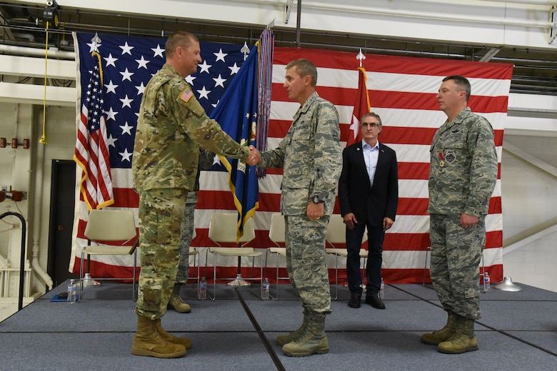 Maj. Gen. Al Dohrmann, the North Dakota adjutant general, left, congratulates Col. Darrin Anderson during a change of command ceremony at the North Dakota Air National Guard Base, Fargo, N.D., Aug. 4, 2018. Anderson is replacing Col. Britt Hatley, far right, the out-going 119th Wing commander.