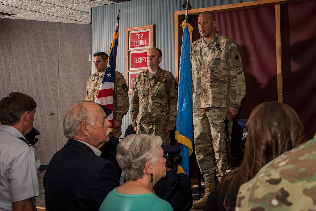 Master Sgt. Adam Hinsperger (left), 285th Special Operations Intelligence Squadron (SOIS) intelligence analyst, Master Sgt. Casey Ray (middle), 285th SOIS intelligence analyst, and Major General Michael Thompson, Adjutant General for Oklahoma, stand at attention as the color guard exits after the playing of the National Anthem during an award ceremony Aug. 4, 2018, at Will Rogers Air National Guard Base, Oklahoma City.