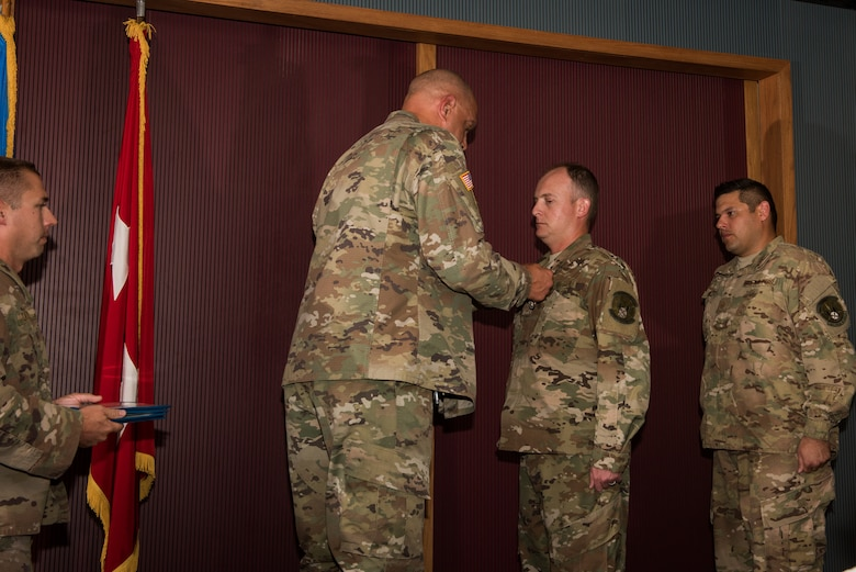 Major General Michael Thompson, Adjutant General for Oklahoma, pins a medal on Master Sgt. Casey Ray, 285th Special Operations Intelligence Squadron (SOIS) intelligence analyst, as Master Sgt. Adam Hinsperger, 285th SOIS intelligence analyst, waits to receive his award during an award ceremony Aug. 4, 2018, at Will Rogers Air National Guard Base, Oklahoma City.
