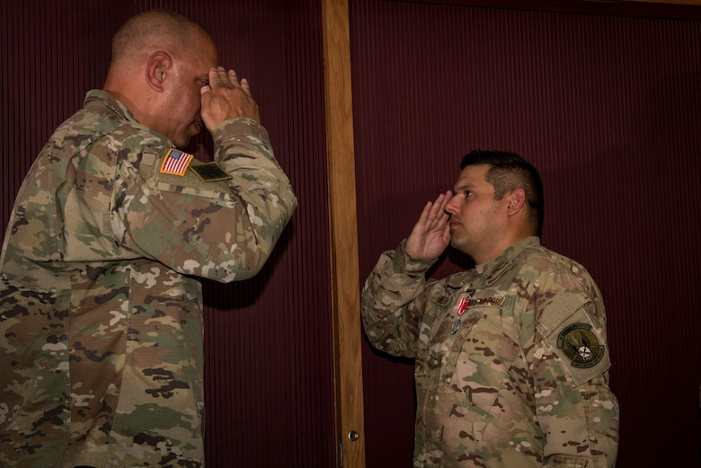 Master Sgt. Adam Hinsperger (left), 285th Special Operations Intelligence Squadron (SOIS) intelligence analyst, salutes Major General Michael Thompson, Adjutant General for Oklahoma, after receving a medal during an award ceremony Aug. 4, 2018, at Will Rogers Air National Guard Base, Oklahoma City.