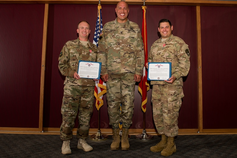 Master Sgt. Casey Ray (left), 285th Special Operations Intelligence Squadron (SOIS) intelligence analyst,  Major General Michael Thompson, Adjutant General for Oklahoma, and Master Sgt. Adam Hinsperger (right), 285th SOIS intelligence analyst, pose during an award ceremony Aug. 4, 2018, at Will Rogers Air National Guard Base, Oklahoma City.