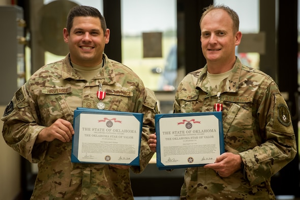 Master Sgt. Adam Hinsperger (left), 285th Special Operations Intelligence Squadron (SOIS) intelligence analyst, and Master Sgt. Casey Ray (middle), 285th SOIS intelligence analyst, pose with their Star of Valor awards Aug. 4, 2018, at Will Rogers Air National Guard Base, Oklahoma City.