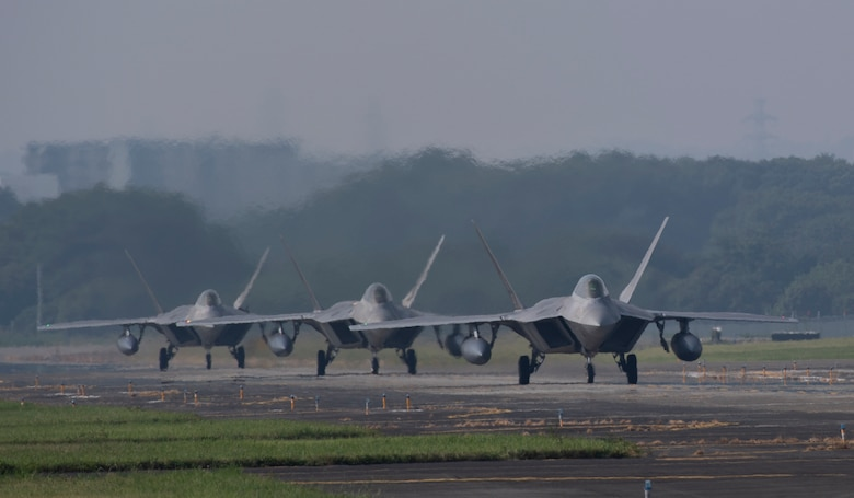 Three F-22 Raptors from Joint Base Elmendorf-Richardson, Alaska taxi down the flightline at Yokota Air Base