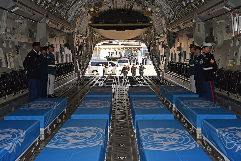 The United Nations Command Honor Guard transfers caskets of remains onto waiting C-17 Globemaster IIIs at Osan Air Base, Republic of Korea, Aug. 1, 2018.
