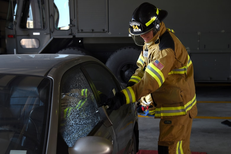 U.S. Air Force Chief Master Sgt. Franklin Chism, 51st Mission Support Group superintendent, breaks the window of a vehicle during an immersion tour with the 51st Civil Engineer Squadron Fire and Emergency Services flight at Osan Air Base, Republic of Korea, Aug. 3, 2018. Not only did leadership get a taste of fighting fires, they also learned other aspects of the firefighters' job such as search and rescue. (U.S. Air Force photo by Senior Airman Kelsey Tucker)