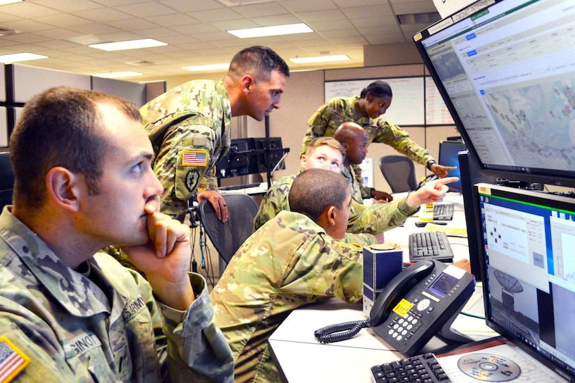 Soldiers gather around computers.
