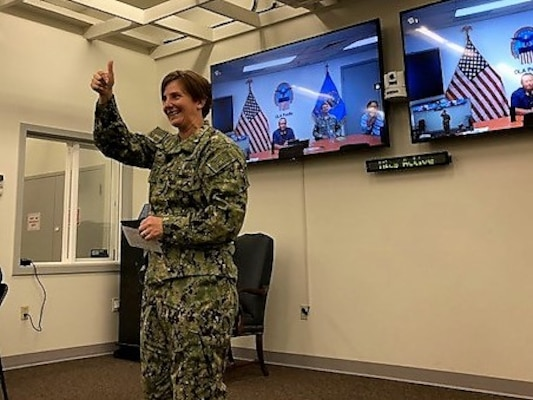 Navy captain in fatigues, addressing audience, holdling 'thumbs up' gesture