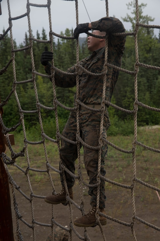 Marine with Charlie Company, 1st Battalion, 23rd Marine Regiment, competing in the 4th Marine Division Annual Rifle Squad Competition, tackle a two-hour timed obstacle course at Joint Base Elmendorf-Richardson, Anchorage, Alaska, August 3, 2018. Super Squad Competitions were designed to evaluate a 14-man infantry squad throughout an extensive field and live-fire evolution. (U.S. Marine Corps photo by Lance Cpl. Samantha Schwoch/released)