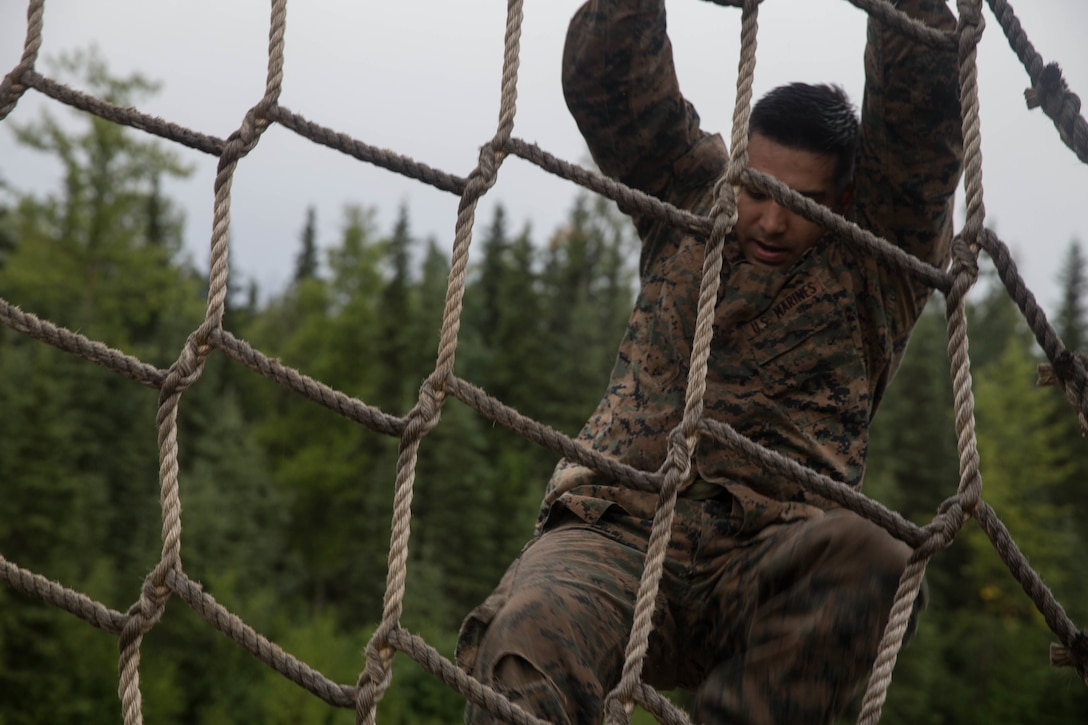 Marines with Charlie Company, 1st Battalion, 23rd Marine Regiment, competing in the 4th Marine Division Annual Rifle Squad Competition, tackle a two-hour timed obstacle course at Joint Base Elmendorf-Richardson, Anchorage, Alaska, August 3, 2018. Super Squad Competitions were designed to evaluate a 14-man infantry squad throughout an extensive field and live-fire evolution. (U.S. Marine Corps photo by Lance Cpl. Samantha Schwoch/released)
