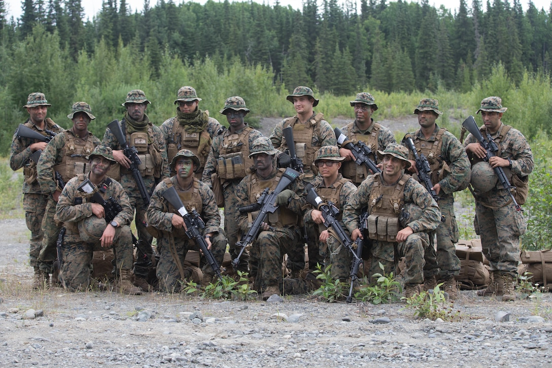 Marines with Charlie Company, 1st Battalion, 23rd Marine Regiment, competing in the 4th Marine Division Annual Rifle Squad Competition, pose for a photo at Joint Base Elmendorf-Richardson, Anchorage, Alaska, Aug. 3, 2018. Super Squad Competitions were designed to evaluate a 14-man infantry squad throughout an extensive field and live-fire evolution. (U.S. Marine Corps photo by Lance Cpl. Samantha Schwoch/released)