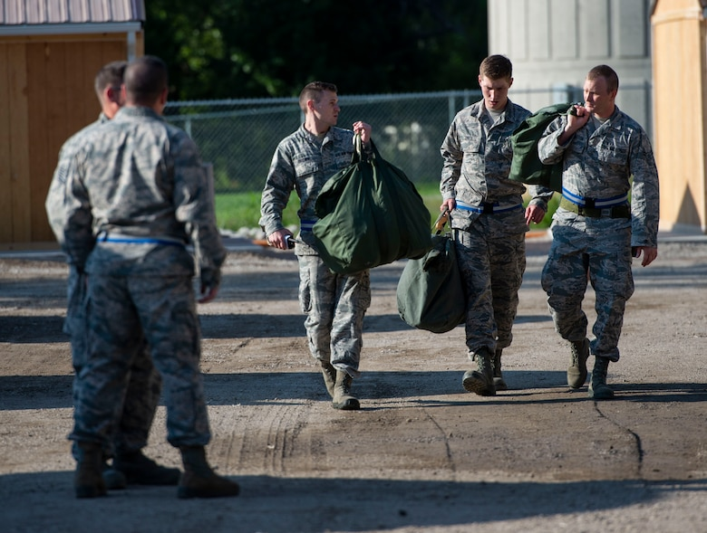 Airmen carry their gear to their tent during a base exercise, Aug. 1, 2018, at Scott Air Force Base, Illinois. The two-phase exercise lasted five days and tested Airmen's ability to respond to explosions and chemical attacks. (U.S. Air Force photo by Airman 1st Class Tara Stetler)
