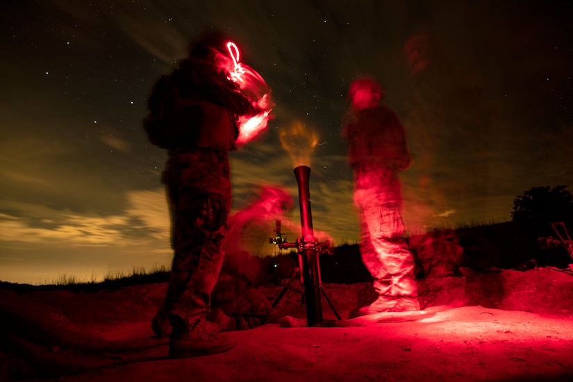 Marines fire a mortar at night.