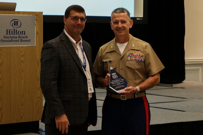 Colonel William Gray, commanding officer of 6th Marine Corps District, Eastern Recruiting Region, Marine Corps Recruiting Command, accepts a gift from Mike Moyer, executive director of the National Wrestling Coaches Association (NWCA) in Daytona Beach, Florida, on Aug 1, 2018. The Marine Corps partnered with NWCA to discuss leadership techniques and recruiting tactics. (U.S. Marine Corps photo by Sgt. Tony Simmons)