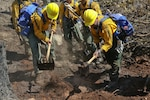Army National Guardsmen and firefighters dig a trench to stop the a fire from spreading.