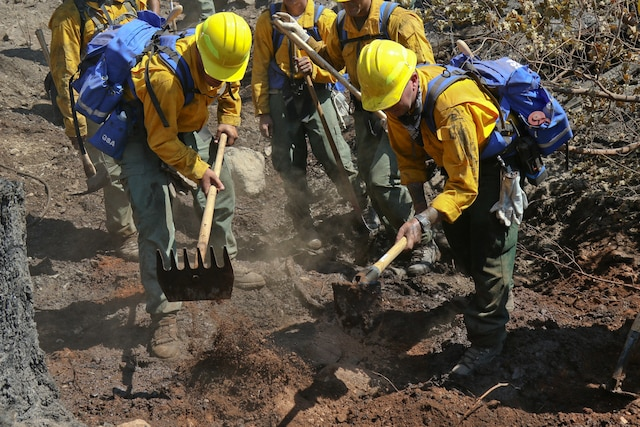 Army National Guardsmen and firefighters dig a trench to stop a fire from spreading.