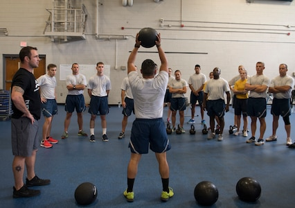 Airman 1st Class Eddie Delgado, an aircrew flight equipment inspector with the 437th Operations Support Squadron, demonstrates a slam ball squat throw during the Alpha Warrior Air Force Fitness Tour Level 1 Battle Rig Instructor Course Aug. 1, 2018, at the Fitness Center at Joint Base Charleston, S.C.