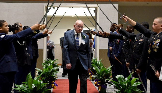 Elwood Burnette, Purple Heart honoree, walks under a sabre salute tunnel during a Purple Heart Banquet and Ceremony at the Maxwell Center Goldsboro, North Carolina, Aug. 3, 2018. The Purple Heart ceremony is conducted to honor Purple Heart recipients, Gold Star families and post-military deceased veteran's families. (U.S. Air Force photo by Tech. Sgt. Phillip Butterfield)