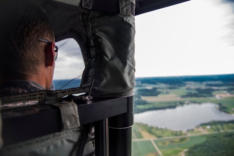 Airman 1st Class Silas Westrick, a security forces member with the 115th Fighter Wing, Truax Field, Wisconsin, looks out the window of a UH-60 Black Hawk helicopter while in flight from Truax Field to Volk Field July 25, 2018. Westrick was a participant of the 2018 Junior Enlisted Orientation Program which allows junior enlisted Airmen to better understand the mission of all the units in the Wisconsin Air National Guard. 