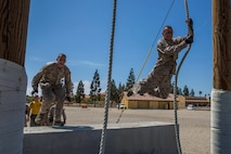 Recruits with Hotel Company, 2nd Recruit Training Battalion, swing across an obstacle during Confidence Course I at Marine Corps Recruit Depot San Diego, July 30.