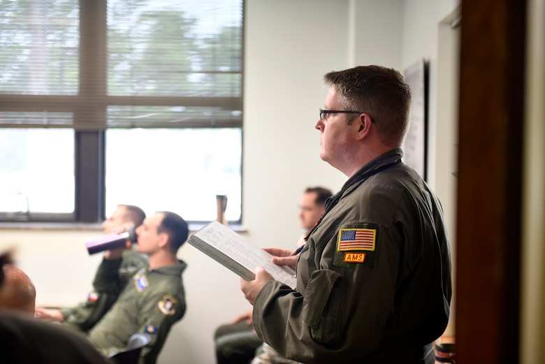 U.S. Air Force Tech. Sgt. Cody Niemi, 97th Intelligence Squadron, listens to a  preflight briefing before departing for a weekend training sortie at Offutt Air Force Base, Nebraska Aug. 5, 2018. The objective of the briefing is to communicate a common operating picture of meteorological and aeronautical information to the entire crew necessary for the conduct of a safe and efficient flight. (U.S. Air Force photo by 2nd Lt. Drew Nystrom)