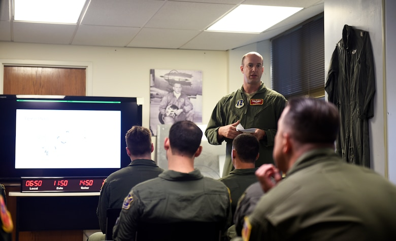 Nebraska National Guard Maj. Ed Merkle, 238th Combat Training Squadron navigator, briefs emergency egress procedures during a preflight briefing before departing for a weekend training sortie at Offutt Air Force Base, Nebraska Aug. 5, 2018. The objective of the briefing is to communicate a common operating picture of meteorological and aeronautical information to the entire crew necessary for the conduct of a safe and efficient flight. (U.S. Air Force photo by 2nd Lt. Drew Nystrom)