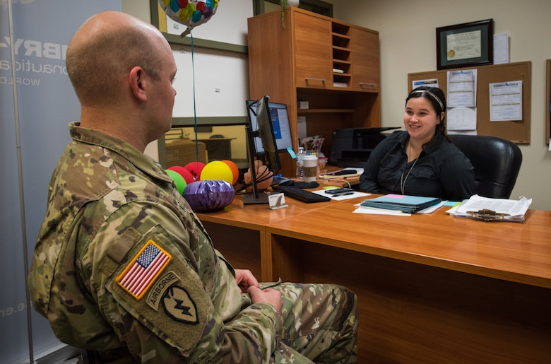 U.S. Army Staff Sgt. Mathew Kelly, assigned to the 1st Squadron (Airborne), 40th Cavalry Regiment, 4th Infantry Brigade Combat Team (Airborne), 25th Infantry Division, U.S. Army Alaska, speaks with Kara Hopkins, Embry-Riddle Aeronautical University associate campus director, at the education center at Joint Base Elmendorf-Richardson, Alaska, Aug. 8, 2018. Embry-Riddle is one of four colleges that offer undergraduate and graduate programs at the education center.