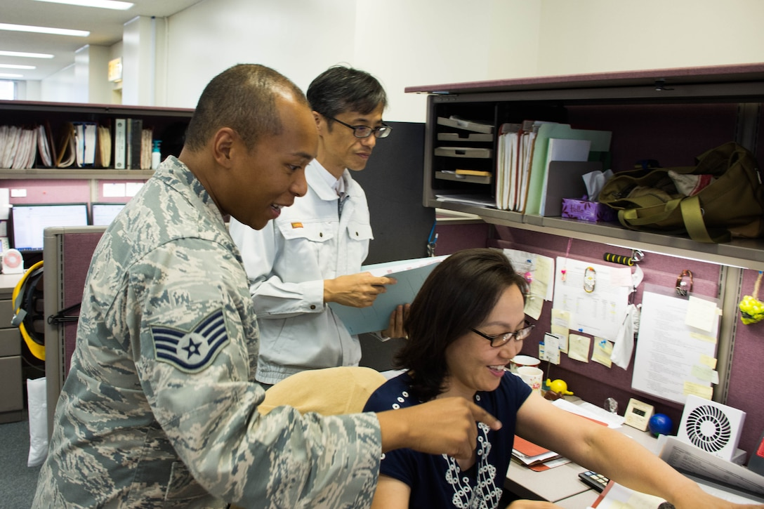 Members from the 374th Contracting Squadron look over a contract to keep U.S. Army base Camp Zama in good repair, Aug 2, 2018, Yokota Air Base, Japan.
