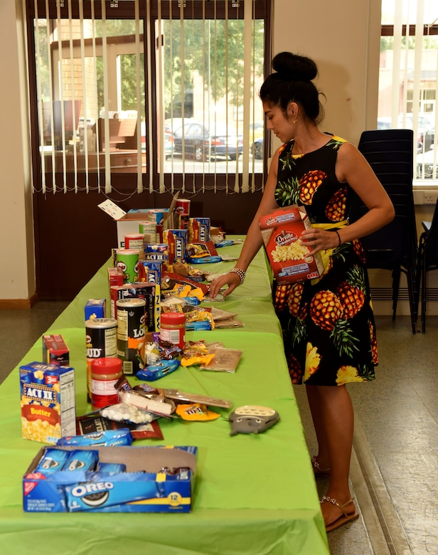 Sarai Boyd, 100th Air Refueling Wing key spouse mentor and volunteer, organizes snacks for care package boxes that are sent to deployed members of wing staff agencies at RAF Mildenhall, England, July 24, 2018. Anyone wishing to either donate items for the care packages, or start up a care package program for their own squadron, should contact their unit's first sergeant. (US. Air Force photo by Senior Airman Lexie West)