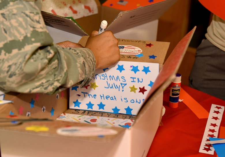 U.S. Air Force Staff Sgt. Brittany McGill, 100th Air Refueling Wing occupational safety craftsman, decorates a care package box for a deployed colleague at RAF Mildenhall, England, July 24, 2018. Each month, a different unit within the wing staff hosts and organizes the event. (US. Air Force photo by Senior Airman Lexie West)