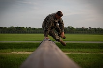 A Marine with Marine Wing Support Squadron 172, Marine Aircraft Group 36, 1st Marine Aircraft Wing, jumps over a log at Camp Hansen, Okinawa, Japan, August 3, 2018. The MWSS-172 Marines participated in the obstacle course together to boost morale and strengthen unit cohesion. The Marines utilize proper technique instead of muscling through the course to reduce risk of injury.