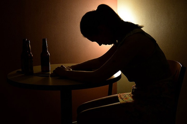 A woman sits in the dark leaning forward on a table.