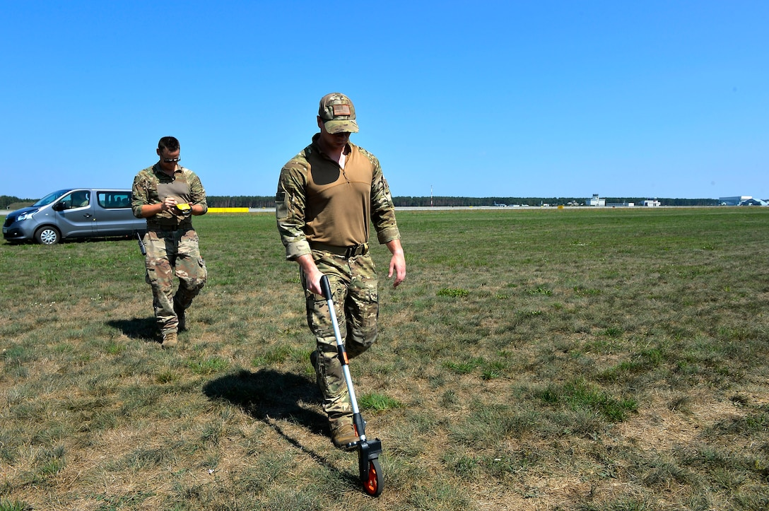 U.S. Air Force Staff Sgt. Matthew Montgomery, front, and Tech. Sgt. Laramie Combs, both 435th Contingency Response Group contingency response air field managers, measure the distance at a landing zone on Powidz Air Base, Poland, Aug. 1, 2018. Contingency response airfield managers use a variety of tools to establish landing and drop zones in austere environments. (U.S. Air Force photo by Senior Airman Joshua Magbanua)