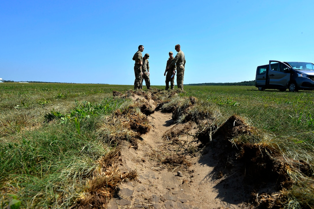 U.S. Airmen assigned to the 435th Contingency Response Group assess a rut generated by an aircraft that landed on Powidz Air Base, Poland, Aug. 1, 2018. Landing zone establishment crews conduct site surveys, assessments, and construction of dirt runways and airdrop targets in a variety of austere environments. (U.S. Air Force photo by Senior Airman Joshua Magbanua)