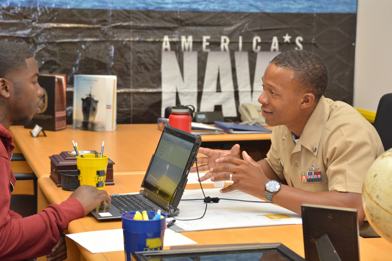 Navy Petty Officer 2nd Class Kristofer D. Wilson, a ship serviceman and recruiter assigned to Navy Recruiting District Los Angeles, speaks to a potential applicant at a recruiting station in Inglewood, Calif., July 18, 2018. Navy photo by Petty Officer 1st Class Richard Perez