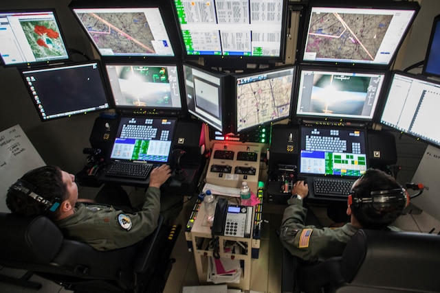 Two Air National Guard pilots sit in front of a wall of computer screens while flying a remotely piloted aircraft.