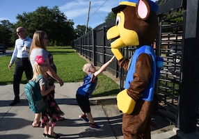 Carson Hunt, son of Tech. Sgt. John Hunt, 333rd Training Squadron instructor, gives a high-five to Chase the Paw Patrol dog on Keesler Air Force Base, Mississippi, Aug. 6, 2018. Keesler children were greeted by members from the 81st Security Forces Squadron, Keesler Fire Department and 81st Force Support Squadron as they went Jeff Davis Elementary School on the first day of school. (U.S. Air Force photo by Kemberly Groue)