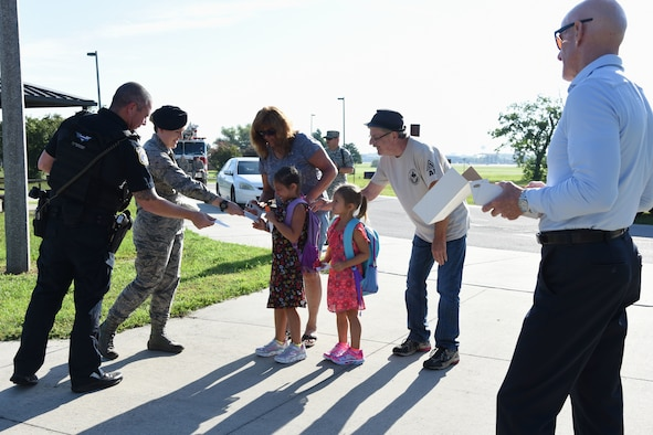 Keesler personnel hand out stickers to Keesler children on Keesler Air Force Base, Mississippi, Aug. 6, 2018. Keesler children were greeted by members from the 81st Security Forces Squadron, Keesler Fire Department and 81st Force Support Squadron as they went to Jeff Davis Elementary School on the first day of school. (U.S. Air Force photo by Kemberly Groue)