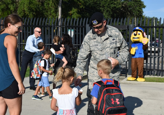 Tech. Sgt. Matthew Oleson, 81st Security Forces Squadron operations NCO in charge, passes out stickers to Keesler children on Keesler Air Force Base, Mississippi, Aug. 6, 2018. Keesler children were greeted by members from the 81st SFS, Keesler Fire Department and 81st Force Support Squadron as they went to Jeff Davis Elementary School on the first day of school. (U.S. Air Force photo by Kemberly Groue)