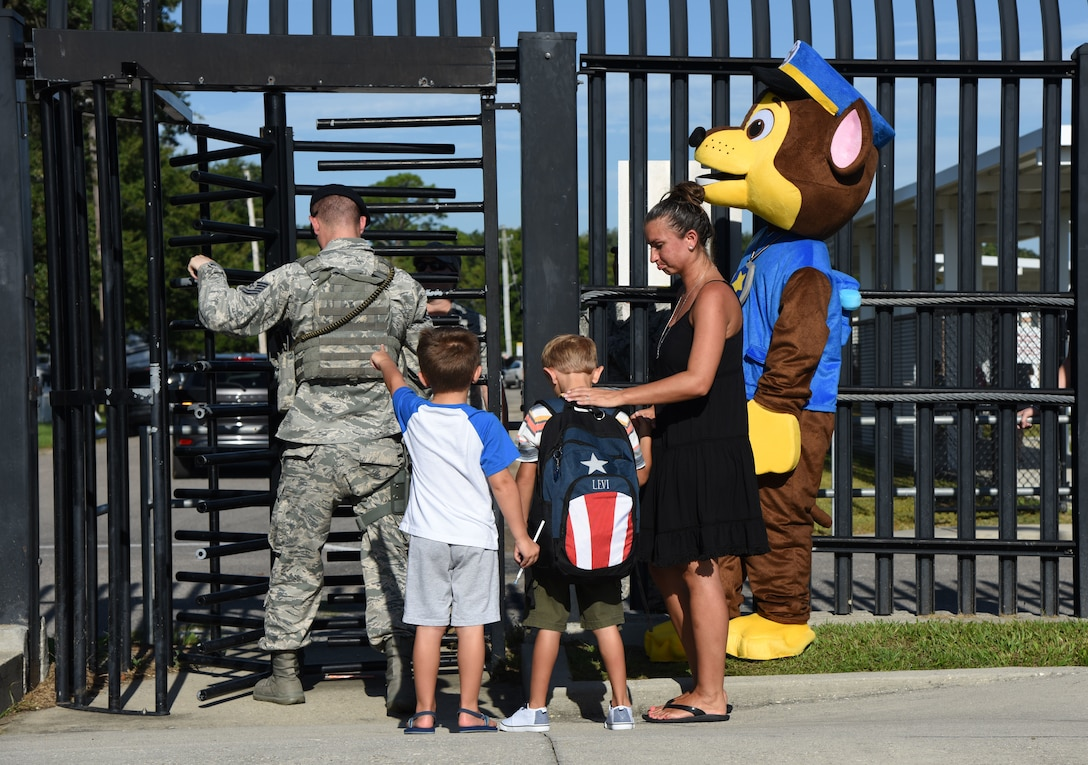 Julia, Levi and Brody, sons of 2nd Lt. Steven Ryan, 81st Medical Group medical administrator, prepare to cross the Jeff Davis Elementary School security gate on Keesler Air Force Base, Mississippi, Aug. 6, 2018. Keesler children were greeted by members from the 81st Security Forces Squadron, Keesler Fire Department and 81st Force Support Squadron as they went to their first day of school. (U.S. Air Force photo by Kemberly Groue)