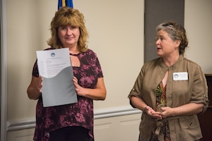 Rachel Anderson, a Delaware Aviation Hall of Fame trustee, right, speaks to retired Senior Master Sgt. Kathleen Lambert, a former 512th Airlift Wing loadmaster, left, during a Delaware Aviation Hall of Fame inductee notification at Dover Air Force Base, Del., Aug. 3, 2018. The Delaware Aviation Hall of Fame selected Lambert as an honoree for her accomplishments as a 512th AW flyer. (U.S. Air Force photo by Staff Sgt. Damien Taylor)