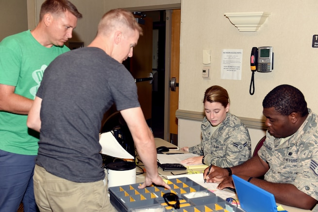 Airman 1st Class Julia McEachin, lodging apprentice, and Staff Sgt. Emuobosan Ojaruega, nightshift lodging non-commissioned officer in charge, both of the 127th Force Support Squadron, Selfridge Air National Guard Base, Mich., provide room assignments at the Alpena Combat Readiness Training center on August 5, 2018. Tech.