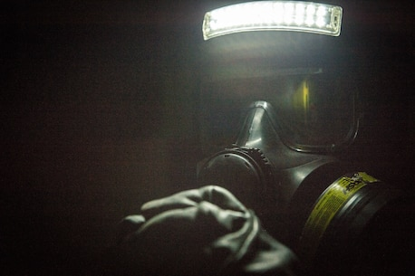 An extract Marine with Chemical Biological Incident Response Force searches for survivors in the dark in a simulated collapsed building during Exercise Chicago Response in Champaign, Illinois July 25, 2018. This was the first time the active duty response force trained with Chicago-area first responders and served to establish a working relationship between CBIRF and the city of Champaign and Chicago.