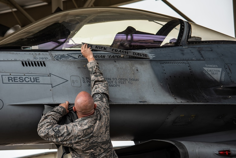 U.S. Air Force Staff Sgt. Tyler Roecker, 20th Aircraft Maintenance Squadron dedicated crew chief, unveils 55th Fighter Squadron (FS) pilot Capt. Brian Davis' name on an F-16CM Fighting Falcon at Shaw Air Force Base, S.C., Aug. 3, 2018.