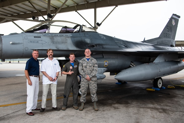 (From left) Retired U.S. Air Force Col. Rick Davis, former F-16 pilot, retired Senior Master Sgt. Daniel Henderson, former dedicated crew chief, Capt. Brian Davis, 55th Fighter Squadron F-16 pilot, and Staff Sgt. Tyler Roecker, 20th Aircraft Maintenance Squadron dedicated crew chief, stand on the flight line at Shaw Air Force Base, S.C., Aug 3, 2018.