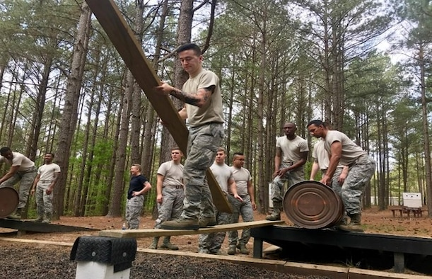 "U.S. Airmen assigned to the 20th Logistics Readiness Squadron work together during ""range control,"" or an obstacle course, at Fort Jackson, S.C., 2018."
