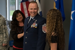 Chief Master Sgt. Jason Evans, 130th Force Support Squadron Chief, gets his new stripes tacked on by his wife and daughter Aug. 4, 2018 at McLaughlin Air National Guard Base, Charleston, W.Va.(U.S. Air National Guard Photo by Airman 1st Class Caleb Vance)